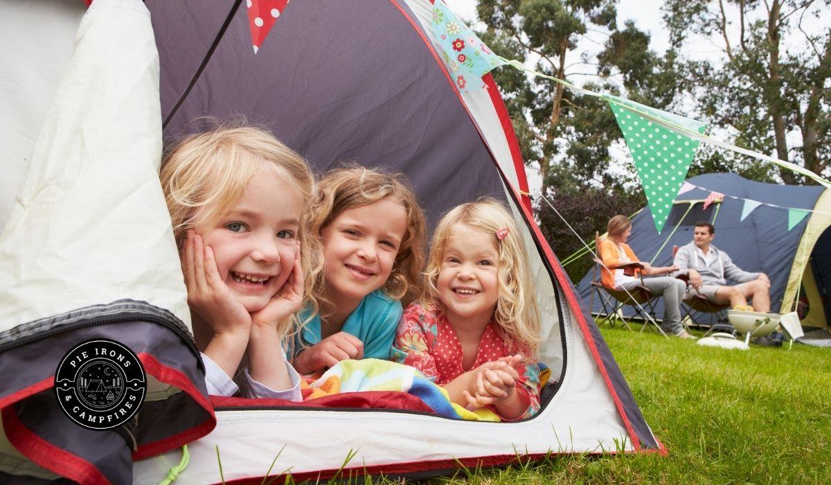 Girls peeking out a tent @ PieIronsAndCampfires.com